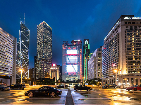 Hong Kong - China - July 4 2019: Luxury sport cars parked on a rooftop parking in Hong Kong Central business district with major bank office building and famous hotels.