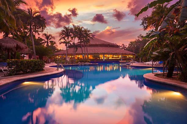 luksusowe swiming basen w tropikalny kurort o zachodzie słońca - kurort turystyczny zdjęcia i obrazy z banku zdjęć