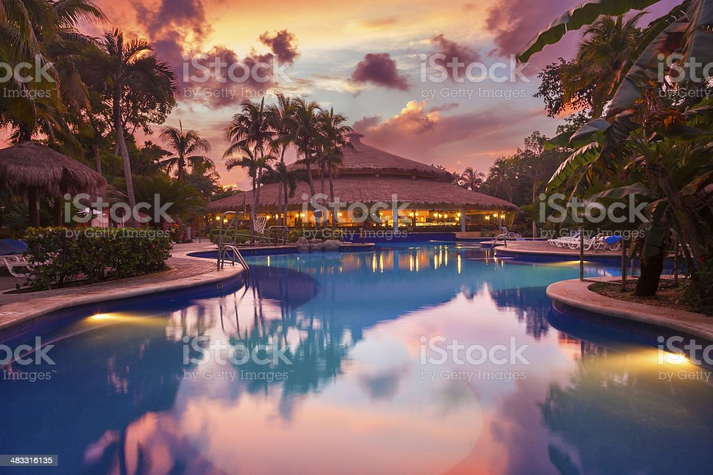 Luxury swiming pool in a tropical resort at sunset stock photo