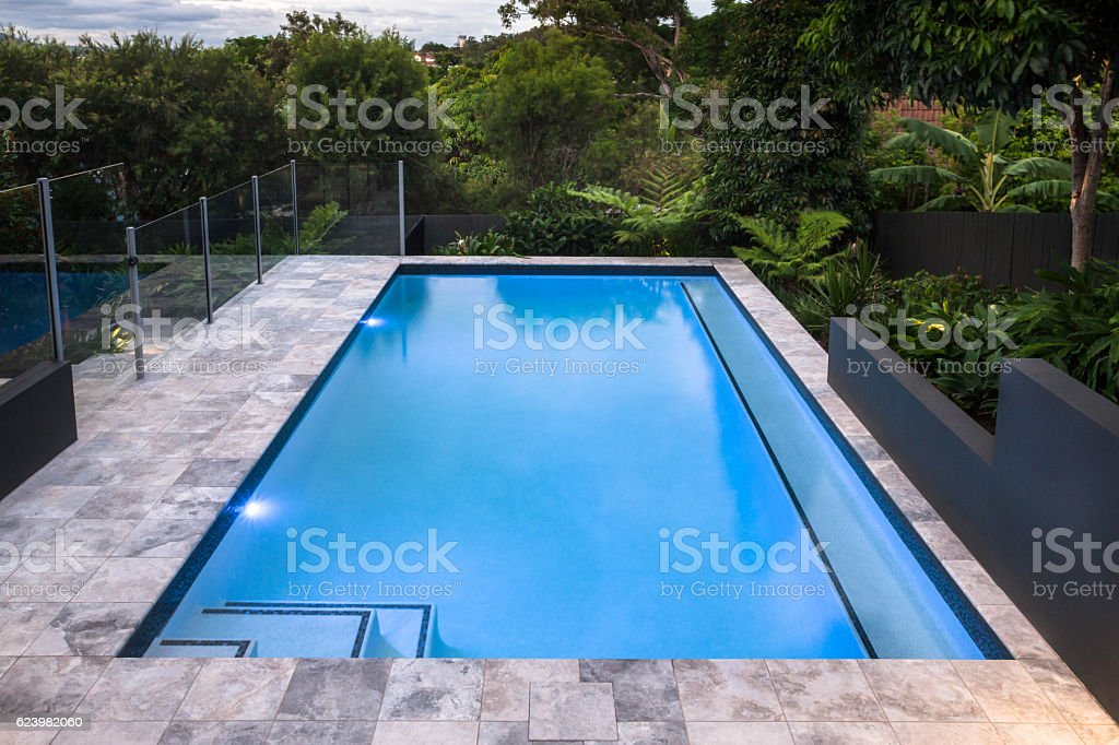 Luxury swimming pool closeup with blue water next to forest stock photo