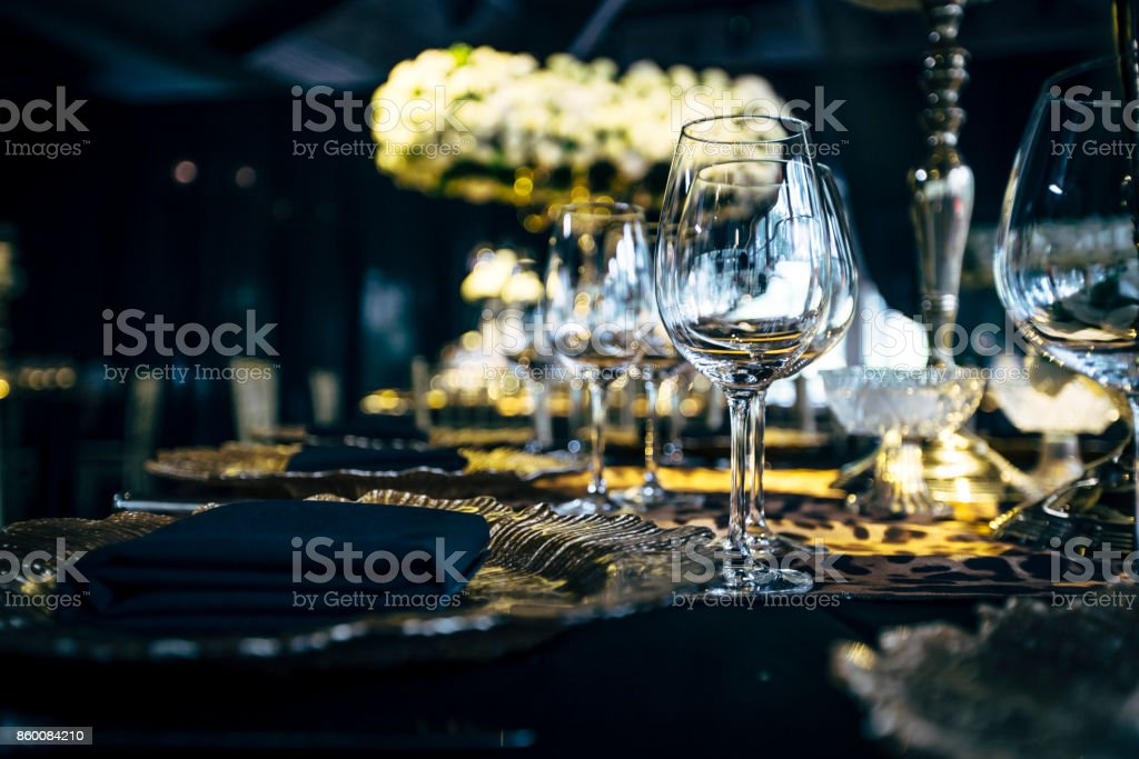 Luxury table settings for fine dining with and glassware, beautiful blurred  background. Preparation for holiday  Christmas and Hannukah dinner night. stock photo