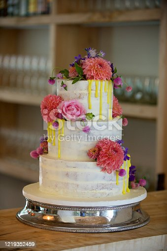 Luxury three layered Wedding cake with colourful flowers and pink roses