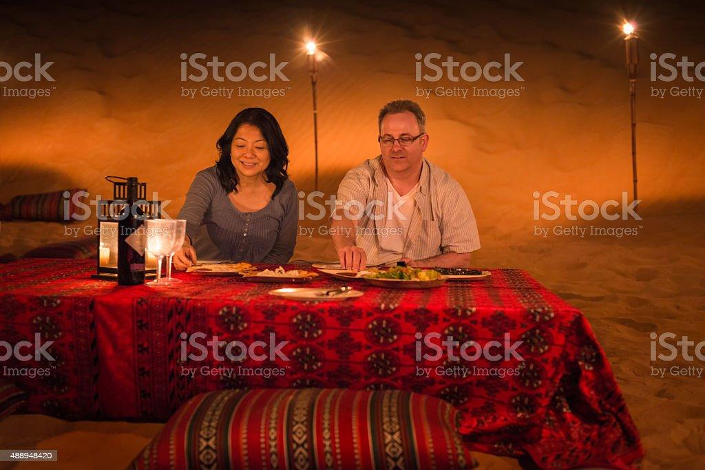 Luxury Travel, Mature Couple Eating Dinner, Desert Camp, Dubai, UAE stock photo