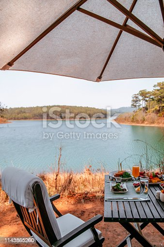 Luxury Tuyen Lam lakeside picnic afternoon tea table set with many food and drinks under white umbrella in Da Lat - Vietnam