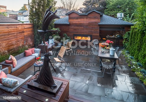 Toronto, Canada - September 23, 2018. Evening view of backyard garden and patio of luxury urban home with back end cabana and slated floor. Sitting area, iron sculpture in the foreground, outdoor fireplace and cabana with BBQ in the background.