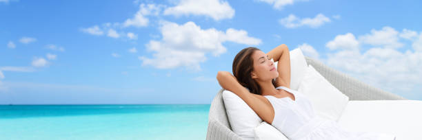 Luxury vacation woman relaxing on beach daybed Asian woman relaxing lounging on white outdoor beach sofa daybed lounger on ocean background luxury vacation. Sleeping girl lying down comfortable enjoying the sun carefree happy. Home living. chaise longue stock pictures, royalty-free photos & images