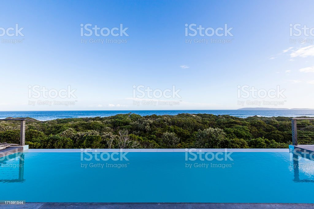 Luxury villa pool deck overlooking forest and ocean royalty-free stock photo