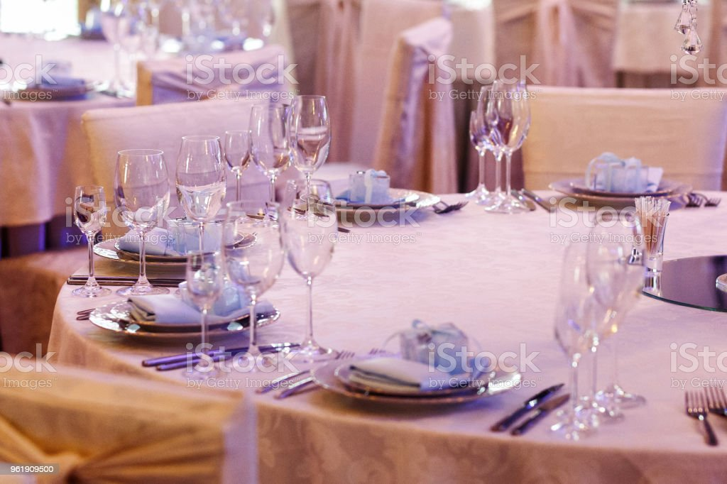 luxury wedding arrangement of stylish glasses plates on napkins and silver cutlery on round table at wedding reception. expensive catering. space for text . decor for feast at holidays stock photo