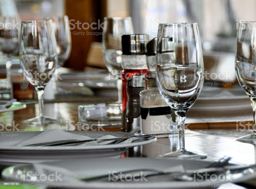 luxury wedding arrangement of stylish glasses plates on napkins and silver cutlery on round table at wedding reception. expensive catering.  decor for feast at holidays. - Royalty-free Arrangement Stock Photo