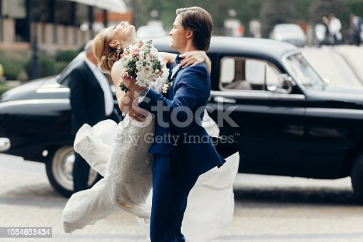 luxury wedding couple dancing at old car in light. stylish bride and groom hugging and embracing in city street. romantic sensual moment. woman looking at man