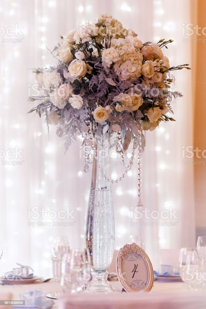 luxury wedding decor with flowers and glass vases and number  of setting on round tables. arrangements of decorations with stones jewels at wedding reception. expensive catering. space for text stock photo