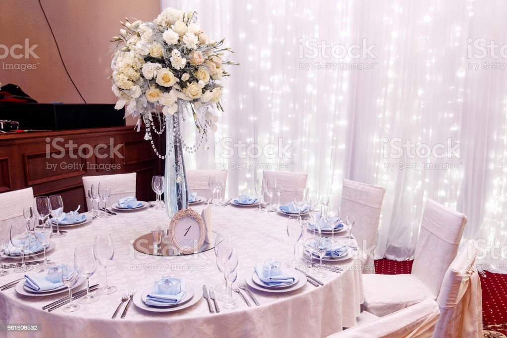 luxury wedding decor with flowers and glass vases and number one of setting on round tables. arrangements of decorations at wedding reception. expensive catering. space for text stock photo