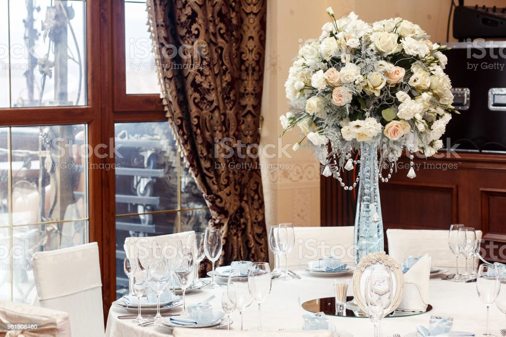 luxury wedding decor with flowers and glass vases with jewels on round tables. arrangements of decorations at wedding reception. expensive catering. space for text stock photo