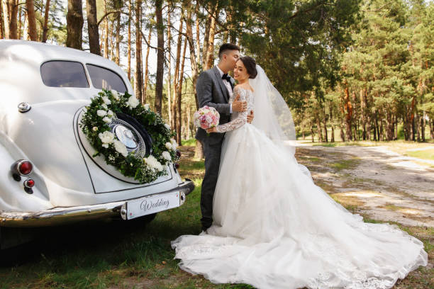 """Luxury wedding photography. Elegant wedding couple, groom in grey suit and bride in wedding dress with long sleeves and long train kissing near white Just Married car with inscription """"Wedding"""" stock photo"""