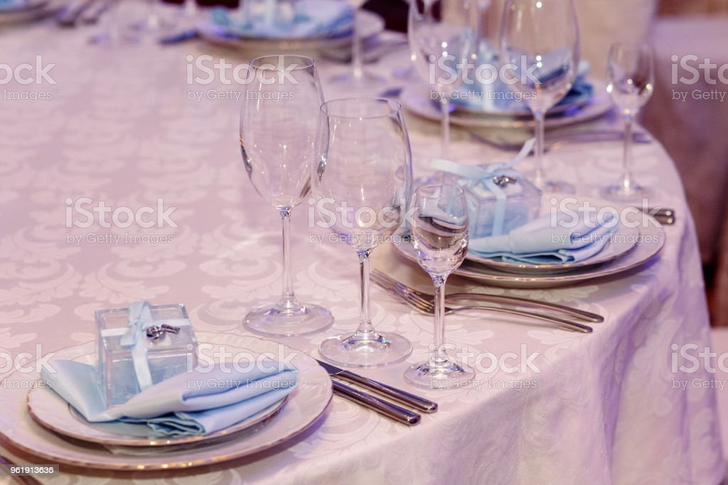 luxury wedding reception. stylish glasses, plates on napkins and silver cutlery and gifts for guest on round table at expensive catering. space for text. decor for feast at holidays stock photo