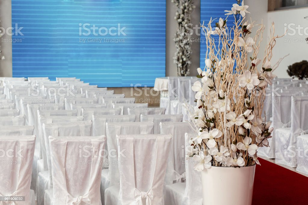 luxury wedding reception with stylish chairs in white silk and orchids. expensive arrangements of decorations at wedding ceremony. space for text stock photo