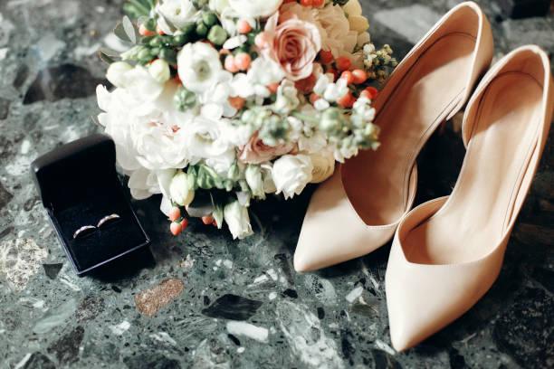 luxus trauringe in black-box in der nähe von schönen weißen blumen brautstrauß und beige hochhackige schuhe, braut-accessoires closeup - goldhochzeitsschuhe stock-fotos und bilder