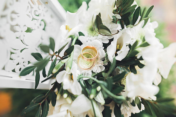 luxury wedding rings lying on the leaves and grass stock photo