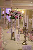 Luxury wedding table decoration. Special event table set up. Fresh flower decoration. Pastel colors. Candles on the table.Close up.