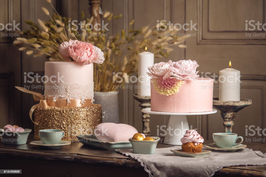 Luxury wedding table with a beautiful pink cake decorated with mastic and rose gold in antique classic interior stock photo