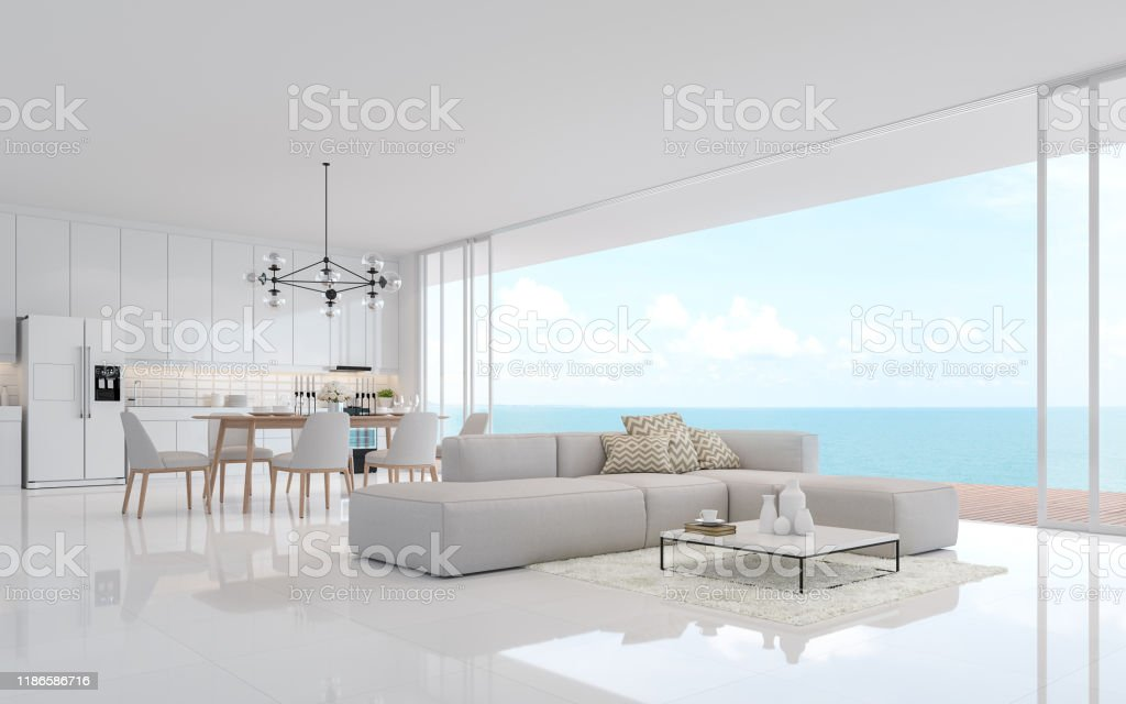 Luxury white living dining room with sea view 3d render Luxury white living dining room with sea view 3d render.There is a minimalistic building interior with white fabric furniture. There is a large open sliding door overlooking the sea view. Architecture Stock Photo