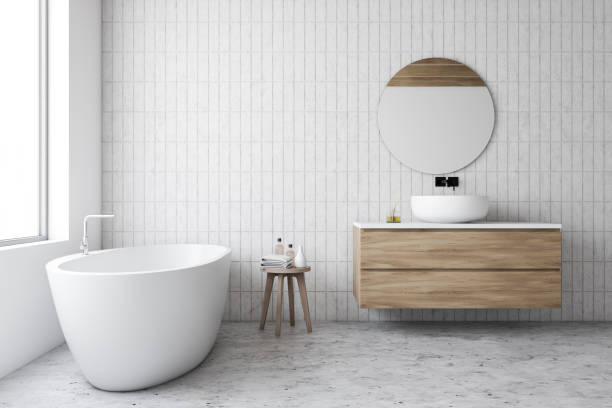 Luxury white tile bathroom, tub and round mirror