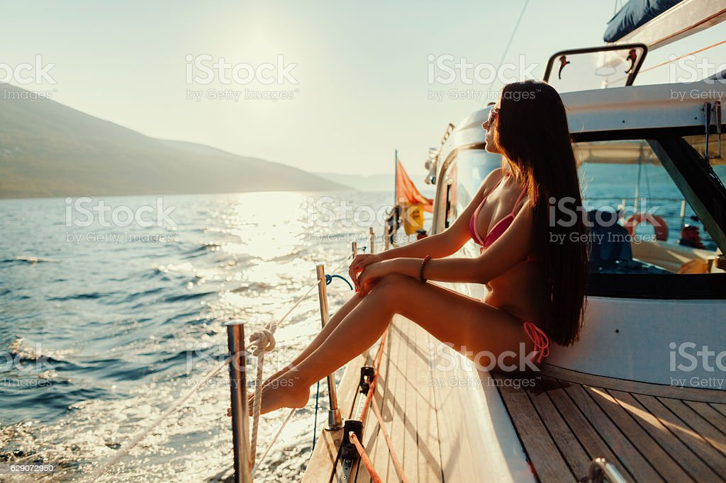 luxury woman yachting in sea at sunset stock photo