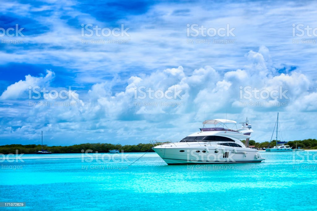 Luxury yacht anchored in a Tropical island turquoise beach royalty-free stock photo