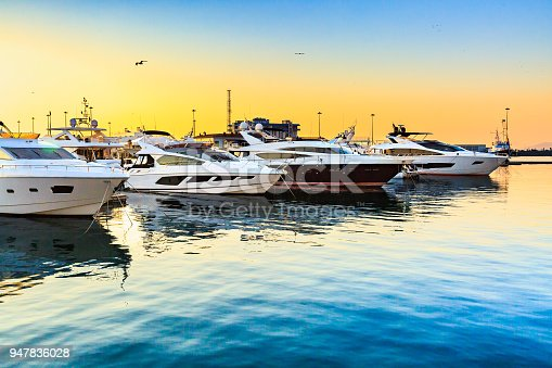 istock Luxury yachts docked in sea port at sunset. 947836028