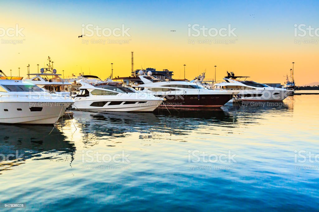 Luxury yachts docked in sea port at sunset. - foto stock