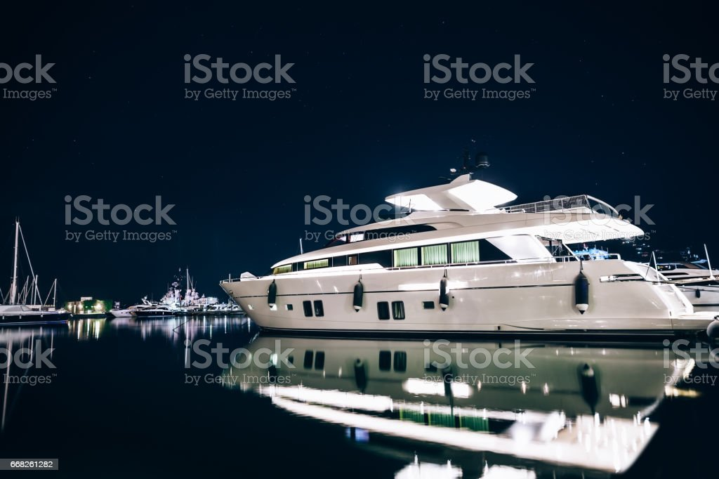 Luxury yachts in La Spezia harbor at night with reflection in water. Italy stock photo