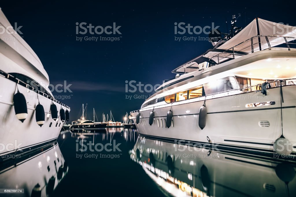 Luxury yachts in La Spezia harbor at night with reflection stock photo