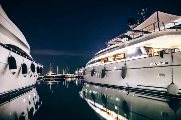 luxury yachts in la spezia harbor at night with reflection - segelyacht stock-fotos und bilder