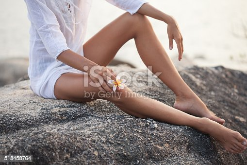 Luxury young woman legs plumeria flower. Thailand, Koh Phangan island