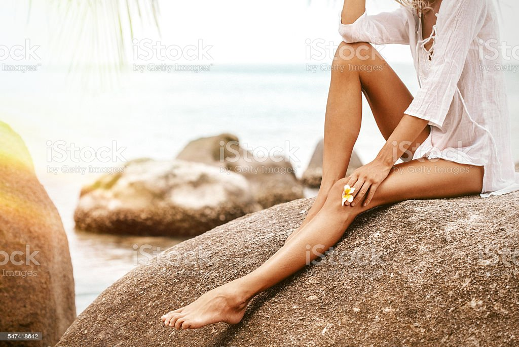 Luxury young woman legs with plumeria flower stock photo