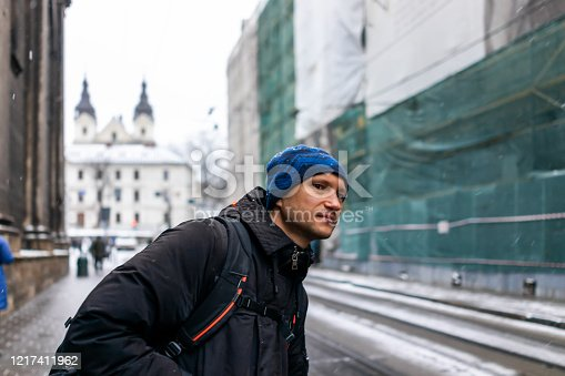 istock Lviv, Ukraine street in old town near market square in winter in Lvov with Christmas cold snow and man in coat backpack travel waiting at bus stop looking 1217411962