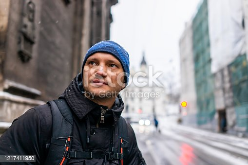 istock Lviv, Ukraine street near old town market square in winter in Lvov with Christmas cold snow and man in coat backpack travel waiting at bus stop 1217411950
