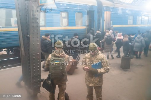 Lviv, Ukraine - December 28, 2019: Interior architecture high angle view of Lvov train station platform in historic Ukrainian city with people soldiers standing in winter boarding