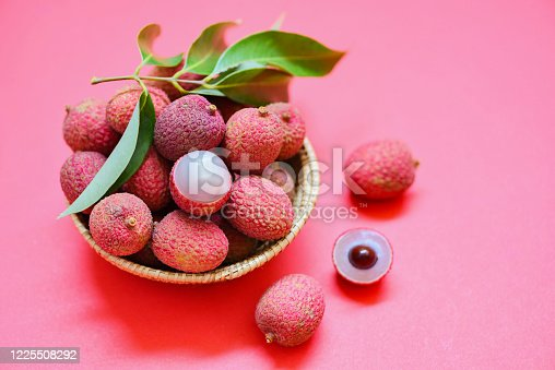 Lychee slice peeled on red pink background / Fresh lychee with green leaves harvest in basket from tree tropical fruit summer in Thailand