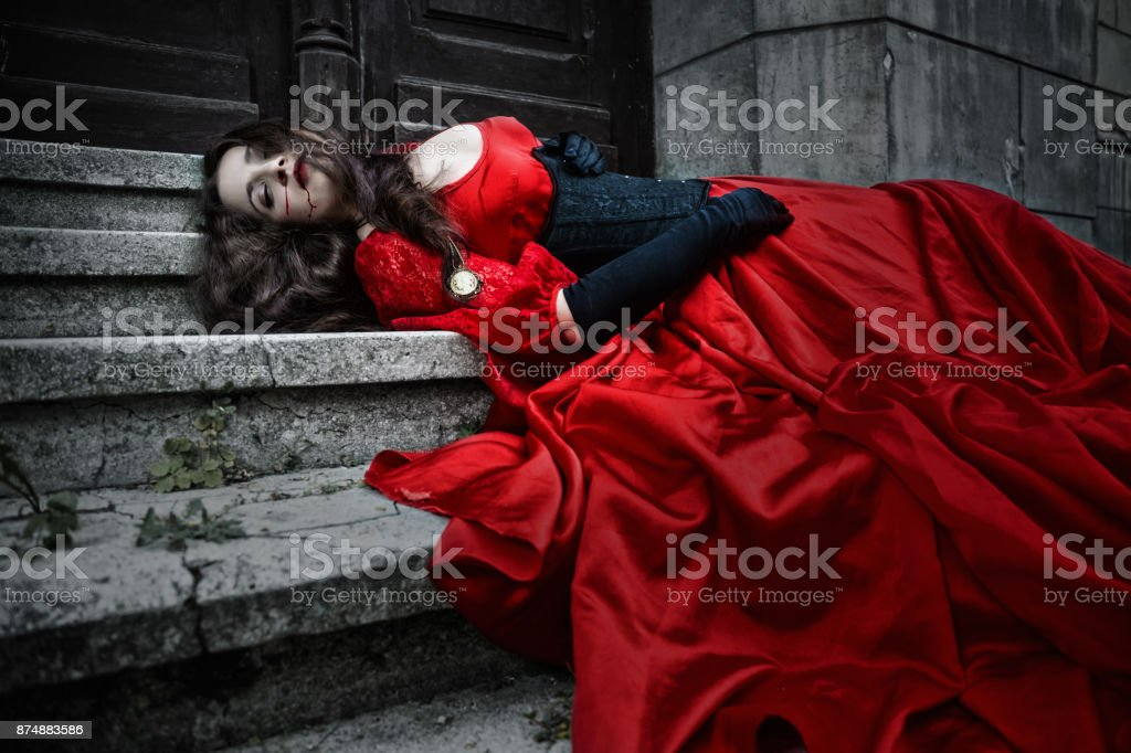 Lying and bleeding woman in a red Victorian dress stock photo