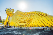 Lying Buddha statue made with blue sky background.