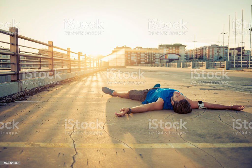 lying down on the floor exhausted after workout stock photo