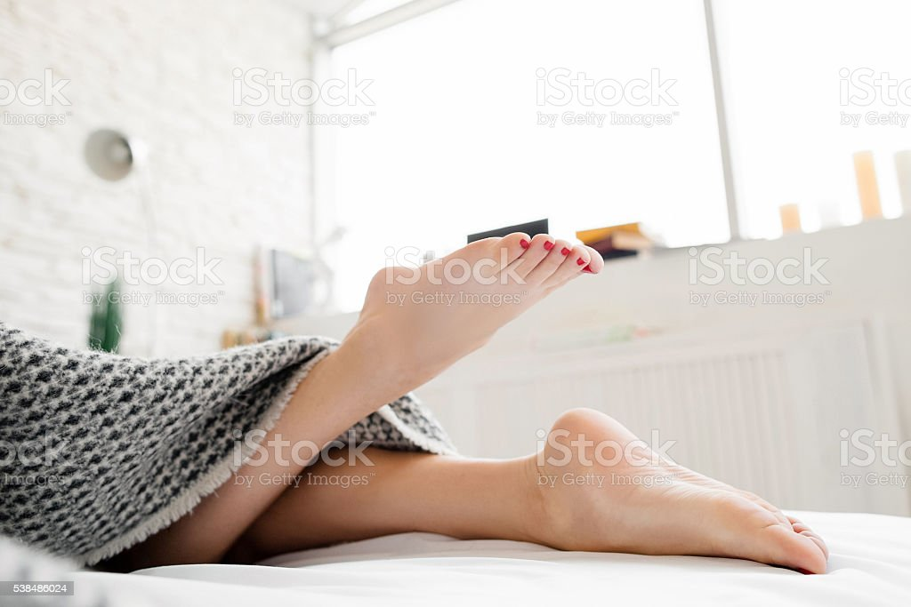 Lying on bed female legs under blanket stock photo