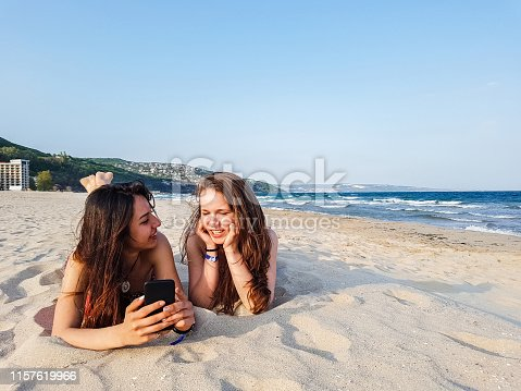Two girlfriends lying on the beach, using mobile phone, having a great time. Picture taken on mobile device. Albena, Bulgaria.