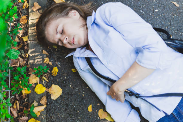 Lying sick woman fainted fainted from heart problem on the ground stock photo