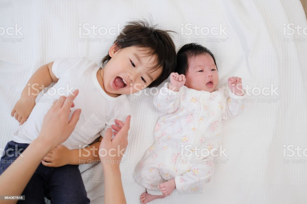 幼児および新生の赤ん坊を横になっています。 ストックフォト
