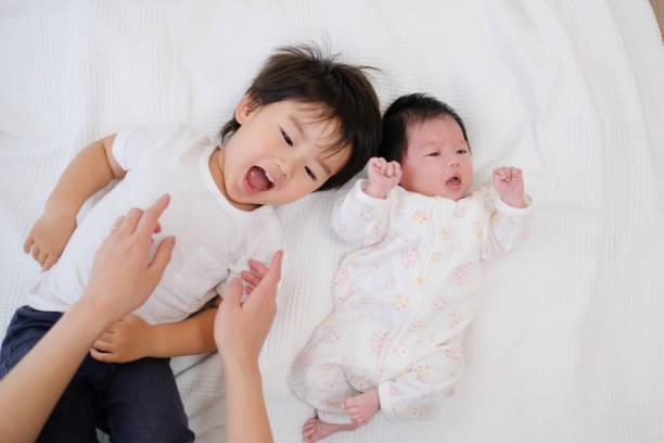 幼児および新生の赤ん坊を横になっています。 - 兄弟 ストックフォトと画像