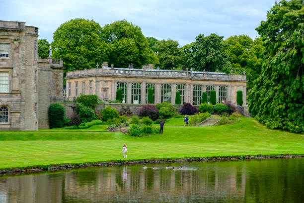 Lyme Hall historic English Stately Home and park in Cheshire with a walking girl and swimming geese in view stock photo