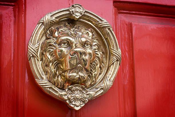 Lyon head door knocker on a red background stock photo