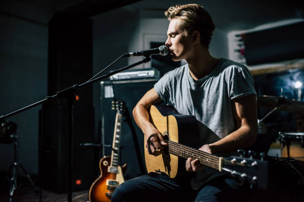 Lyric singer with acoustic guitar. Handsome young man on rehearsal base. Lyric singer with acoustic guitar. guitarist stock pictures, royalty-free photos & images